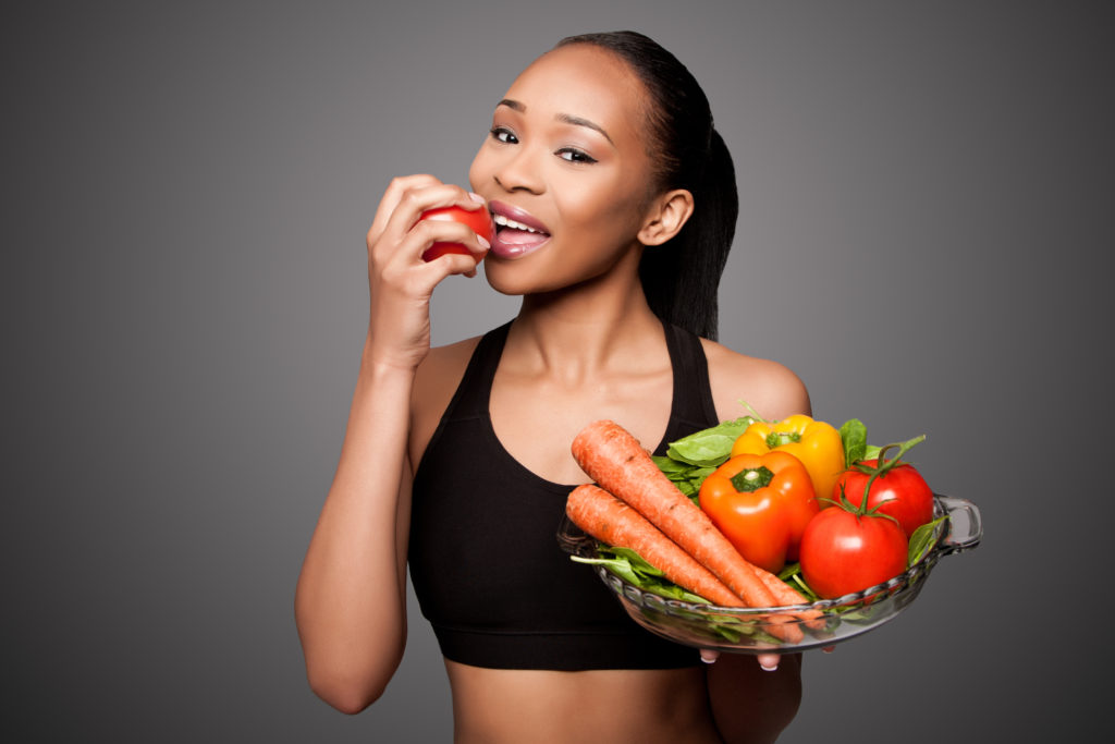 fit attractive woman eating fruit and smiling with nice teeth