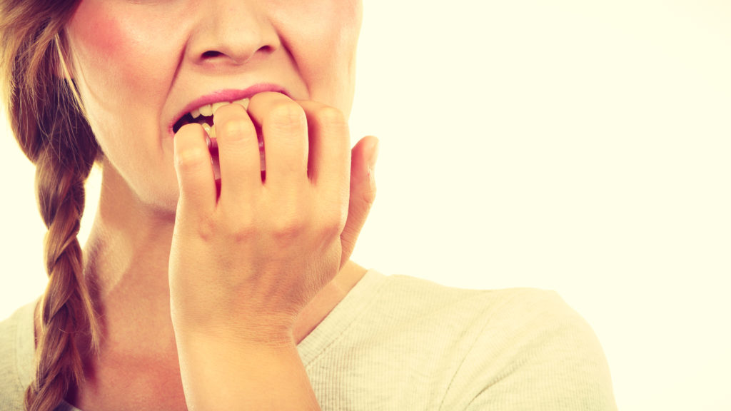woman biting fingernails may have to visit dentist in Marion