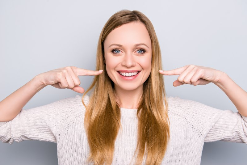Woman pointing to her smile