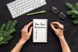woman writing New Year's resolutions